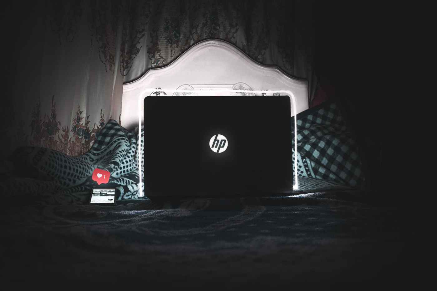 black hp laptop on bed is on